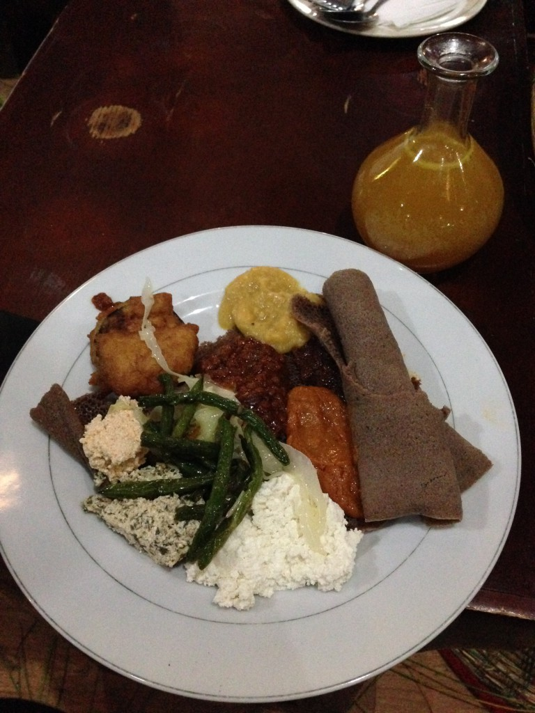 The brown roll is the injera and the rest of the plate is full of different sauces and vegetables.